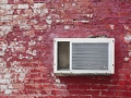 Old AC unit on the old red brick wall.