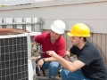 Instructor trains student to repair air conditioning compressor.